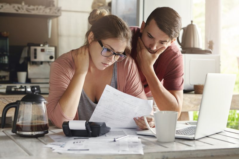 Young family having debt problems, not able to pay out their loan. Female in glasses and brunette man studying paper form bank while managing domestic budget together in kitchen interior