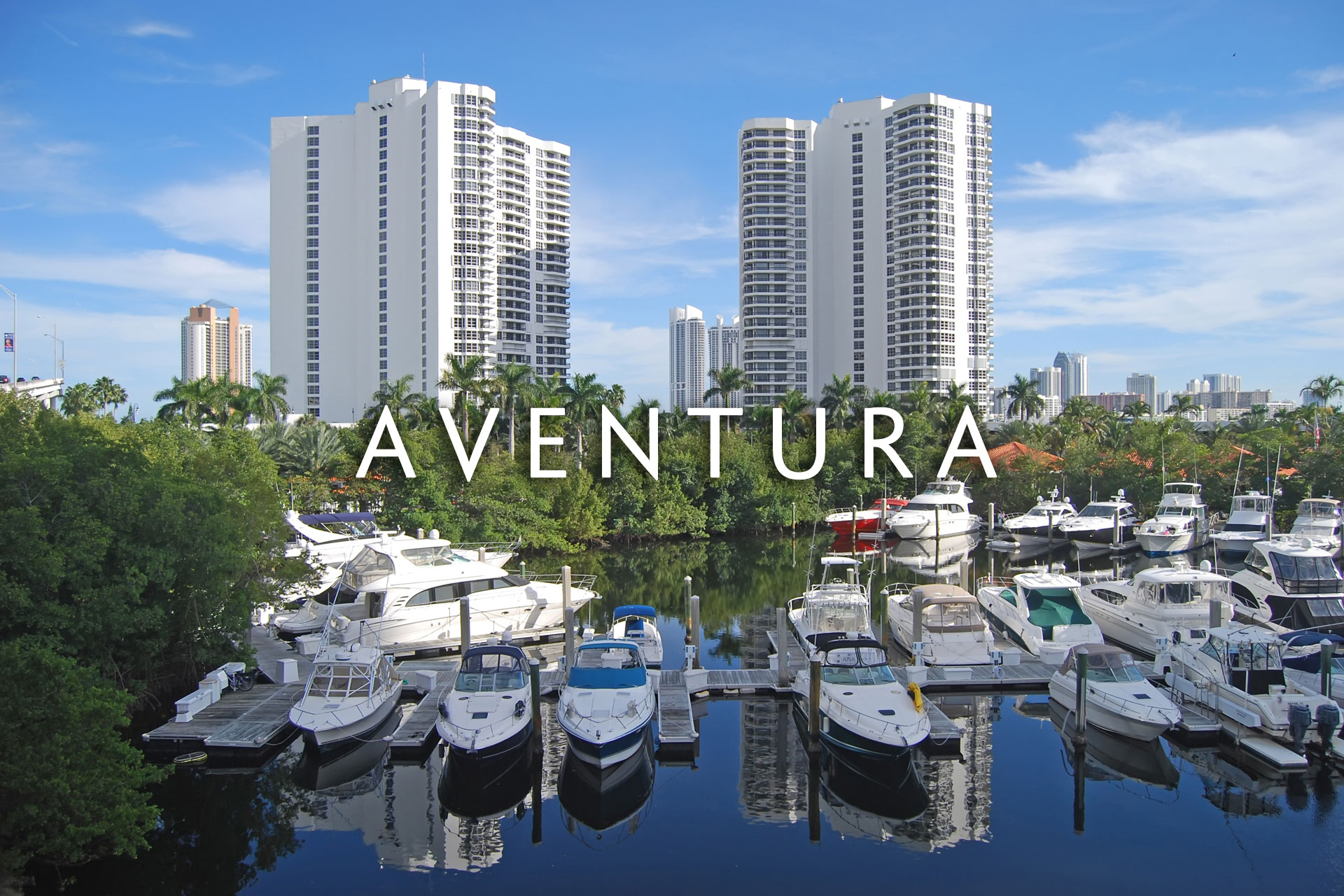 Aventura condo buildings on oceanway with various yachts in front of them
